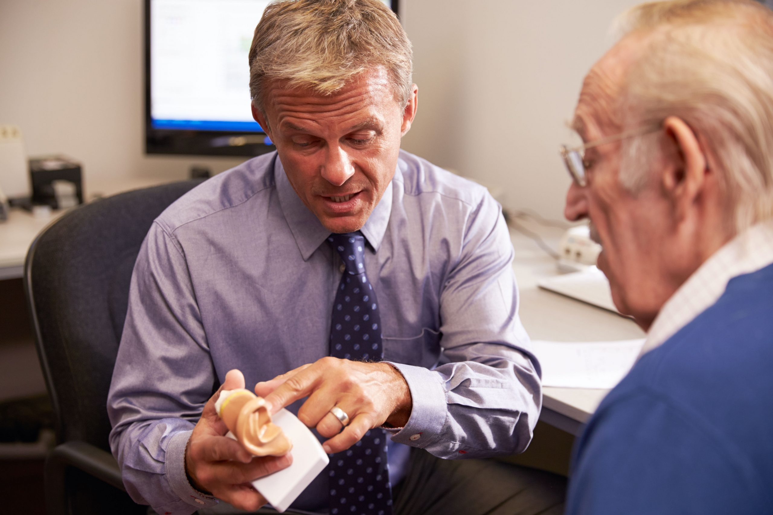 A hearing care practitioner working with a patient